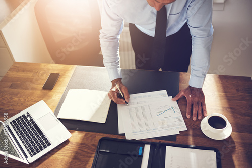 Businessman leaning on his office desk signing documents