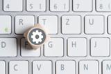 Würfel auf Tastatur mit Getriebesymbol