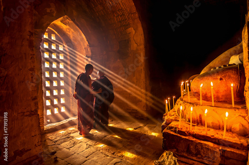 Two asian Burmish monk change the robe with sun ray in pagoda at bagan, mandalay Poster