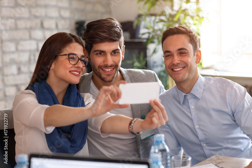Wall mural Colleagues make selfie in office