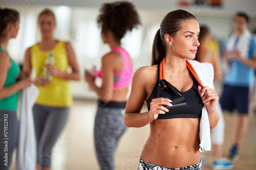 Wall mural Female brunette with towel at gym