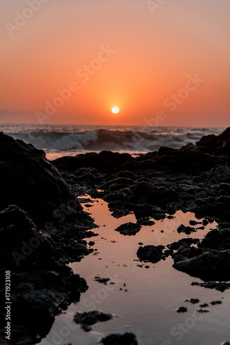 Fotobehang Zee zonsondergang wave on rocks sunset