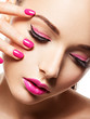 face of a beautiful  girl with pink eye makeup, lips and bright pink  nails.