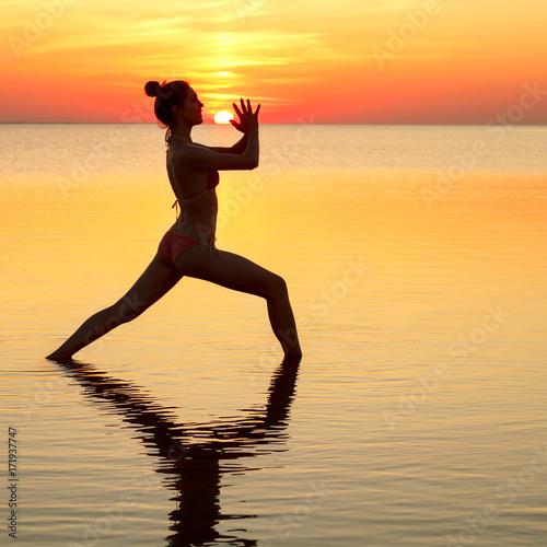 Obraz na płótnie young beautiful brunette woman doing yoga at sunset on beach