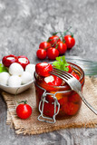 Marinated  cherry tomatoes stuffed with mozzarella and spices on wooden table - 171940554