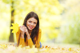 Cute woman laying in autumn park - 171943594