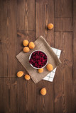 Delicious ripe apricots and raspberries on a wooden background, burlap cloth. Horizontal top view