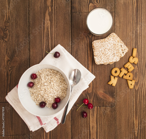 Poster Bowl, bran, milk and fresh cherries, on wooden background, top view