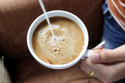 Poster pouring creamer into a cup of coffee