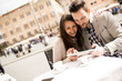 Loving couple looking at the tablet in a cafe in Rome