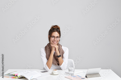 Picture of successful young woman office worker relaxing during coffee break while sitting at her white workplace, making report and studying graphs and financial data. Business and modern technology