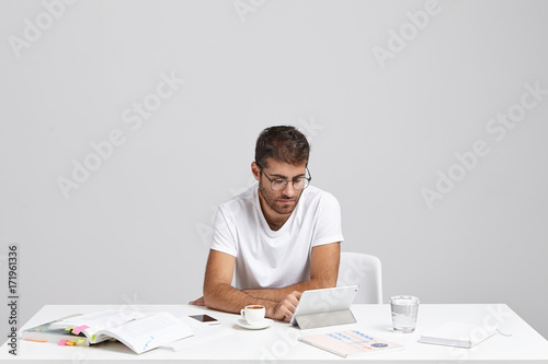 Serious male worker sits at work place checkes email or reads world news on digital tablet computer, uses free internet connection. Male student reads articles, searches information for course paper