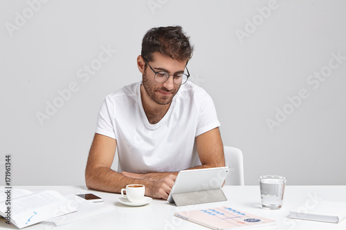Candid shot of handsome bearded modern businessman wearing stylish glasses and casual white t-shirt working at his office desk, using digital tablet, checking financial report and drinking espresso