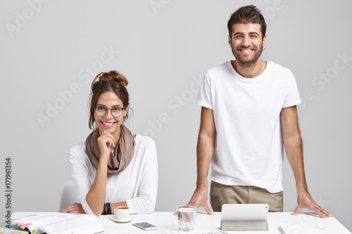 Two successful creative colleagues working together at white office desk. Cheerful unshaven male architect duscussing new architectural project with his female colleague, gadgets and papers on table