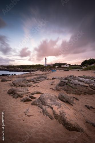 In de dag Ochtendgloren Steiniger Strand vor einem Leuchtturm