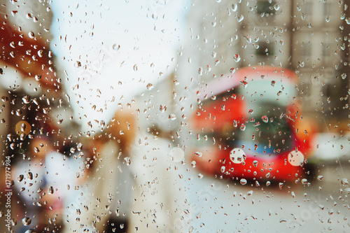 Raindrop on glass and red London bus lights background. Poster