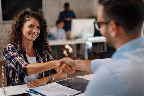 Foto Murales Young woman signing contracts and handshake with a manager
