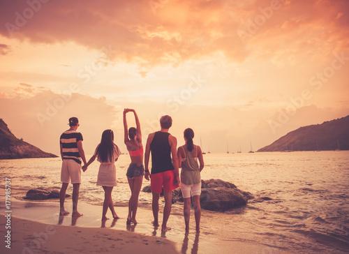 Przyjaciele na plaży o zachodzie słońca
