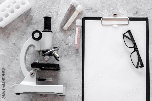 Microscope and tablet on grey stone background top view mockup