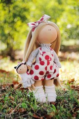handmade doll - girl holds a baby doll in hands