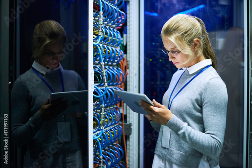 Portrait of young smiling woman checking data on digital tablet while working with supercomputer in research center