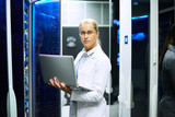 Portrait of young woman wearing lab coat working with supercomputer standing in server room holding laptop - 171997341