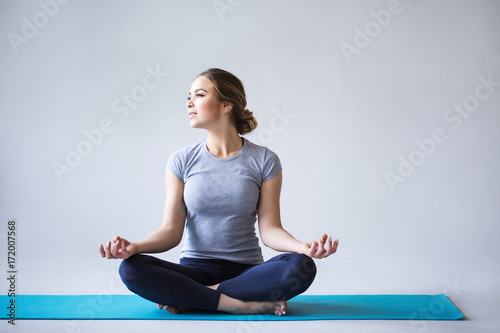 Poster Woman doing yoga and meditating in lotus position in a fitness studio on a gray background.