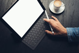 Man using tablet and typing on electronic tablet keyboard-dock station while sitting at wooden table.White blank device screen.Blurred background.Horizontal mockup.