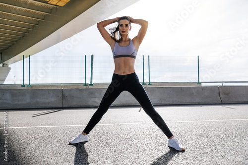 Fotobehang Fitness Fitness woman standing on a road, warming up her body for training