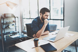 Bearded pensive coworker working at sunny loft office on laptop while sitting at wooden table.Businessman reading documents on notebook display.Blurred background,horizontal.