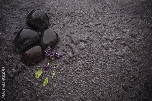black stone with green leaf and smallthe  cute purple flower decoration on stone plate background with copy space for spa and meditation concept background