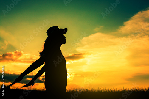 Aluminium Oranje Young woman relaxing in silhouette sunset sky outdoor.