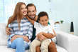 Quadro Happy couple with adopted African-American boy sitting on couch at home