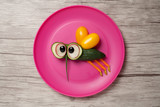 Fly made of cucumber on plate and wooden background
