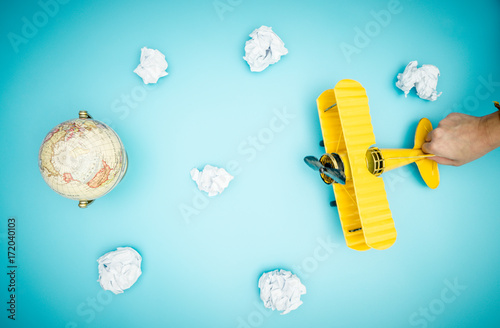 Yellow toy plane is flying to the Earth sky