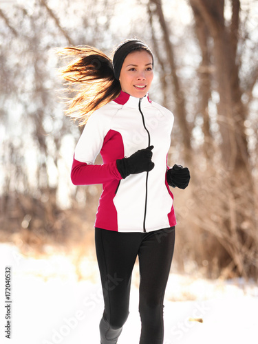 Winter runner woman jogging outside in forest. Jogger fit Asian girl running outdoor breathing cold air wearing sportswear windproof jacket, tights, gloves and ear warmers headband.