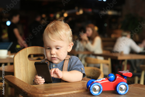 Little boy is sitting in a cafe with telephone