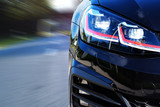Close up of sports car headlights on the road