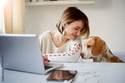 Caucasian businesswoman playing with dog in home office