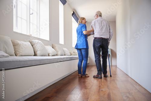 Poster Nurse helping senior man walk using a walking stick