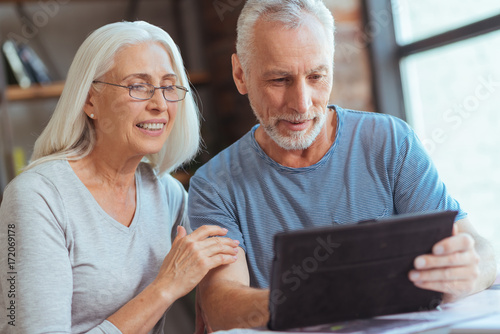 Leinwandbild Motiv Delighted retired couple using tablet at home