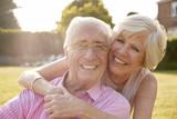 Senior couple in garden, smiling at camera, close up - 172069589