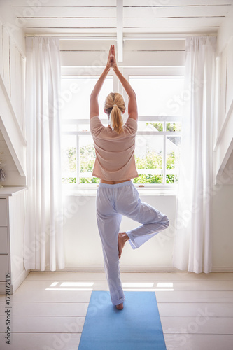 Woman At Home Starting Morning With Yoga Exercises In Bedroom