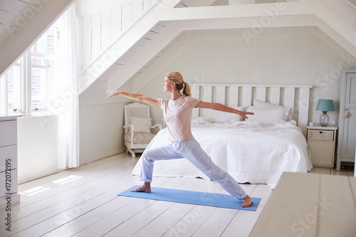 Fototapeta Woman At Home Starting Morning With Yoga Exercises In Bedroom