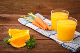 Refreshing orange-carrot juice in a glass on a wooden background. Carrots, orange, mint, Melissa and fruit and vegetable juice. Vitamins. Proper nutrition.