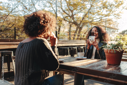 Poster Two women friends drinking coffee and clicking photos