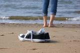 einsames Mädchen barfuß am Strand mit Turnschuhen im Vordergrund - 172118773