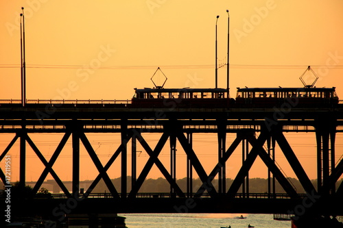 Silhouettes of a two-tiered bridge and 2 trams on a sunset ,  Dnepr city, (Dnepr Plakat