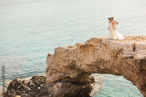 In de dag Cyprus beautiful gorgeous blonde bride and stylish groom standing on rocks, on the background of a sea, wedding ceremony on cyprus.