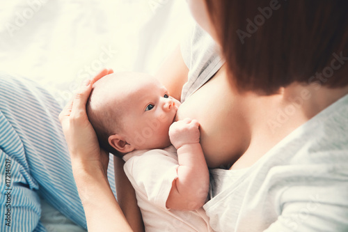 Mother breastfeeding newborn baby at home.